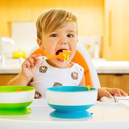 niño pequeño comiendo con cuencos con ventosa